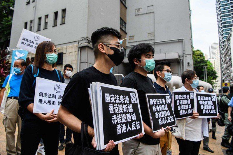 香港民主派示威者22日前往中聯辦舉牌抗議港版國安法。法新社