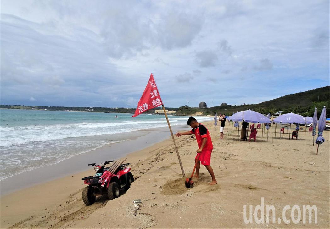 屏東墾丁今天上午多雲偶爾出現陽光,因海邊浪高超高1公尺,救生員在遊憩沙灘插上禁止...