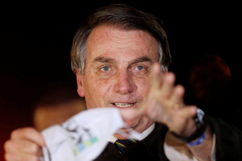 巴西總統波索納洛廿二日一面取下口罩一面回答記者問題。(路透)