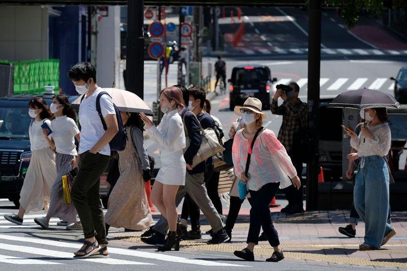 隨著單日確診人數大減,東京澀谷車站周邊、商店街以及上野阿美橫商店街等行人大增。圖/法新社