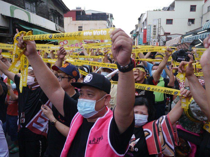 眾人在晚上6點6分舉起手中黃絲帶,高喊「6月6日一起投票罷韓」。記者徐白櫻/攝影