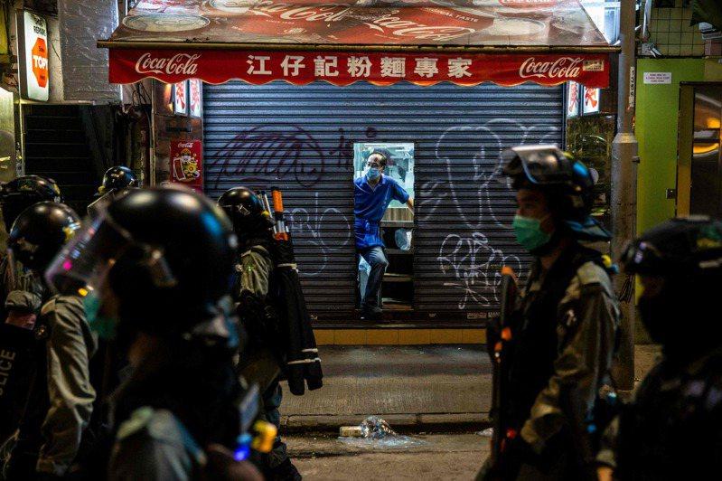 抗議港版國安法,香港街頭再現大型示威及催淚彈。衝突熱點附近的銅鑼灣東角道,大部分商家均拉下鐵閘「關門避禍」。圖/法新社