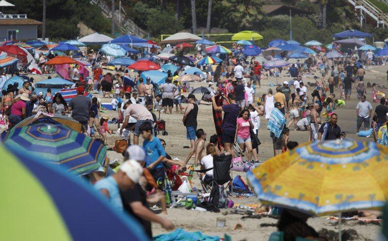 美國鬆綁防疫限制,民眾於陣亡將士紀念日聚集在南加州一海邊。路透