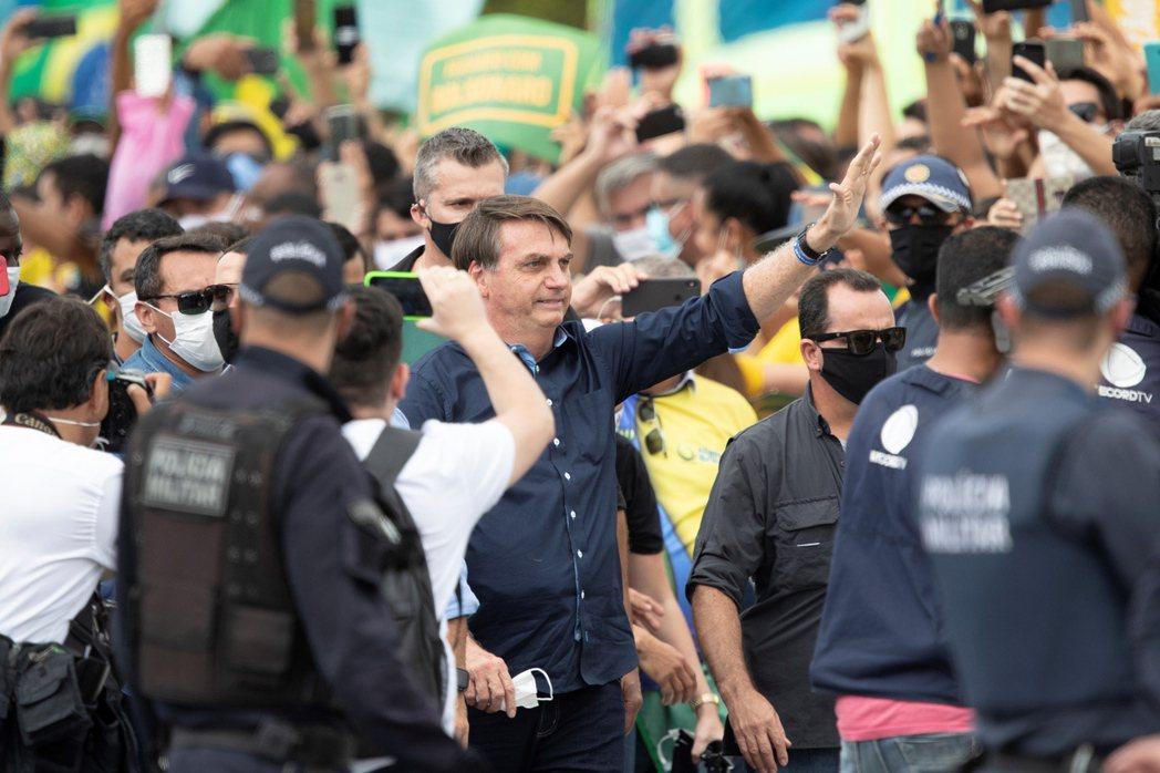 巴西總統波索納洛(中)廿四日在巴西利亞的總統府高原宮前一場示威中和數百名支持者會...