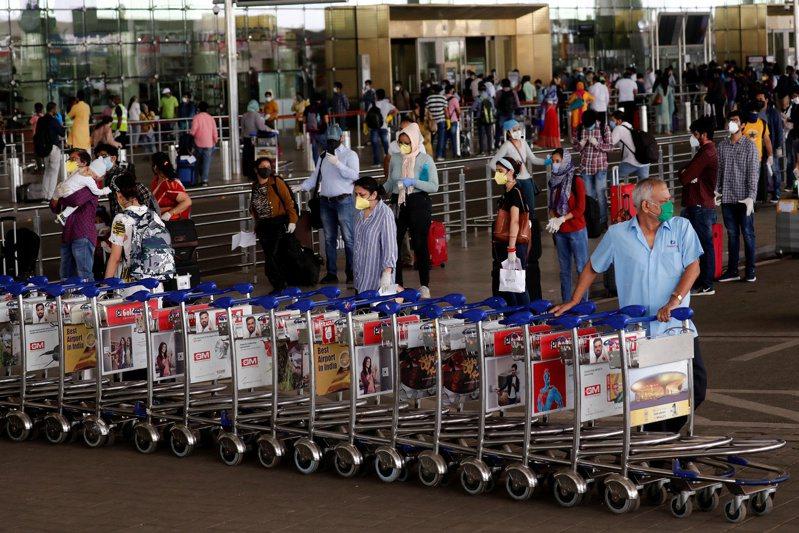 印度25日恢復國內線航班,圖為復飛首日來到孟買機場準備搭機的大批民眾。圖/路透