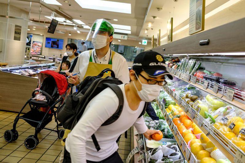 東京一家百貨公司的超市25日恢復營業,消費者(右)拿起橘子,職員(中)戴口罩和面罩工作。(法新社)