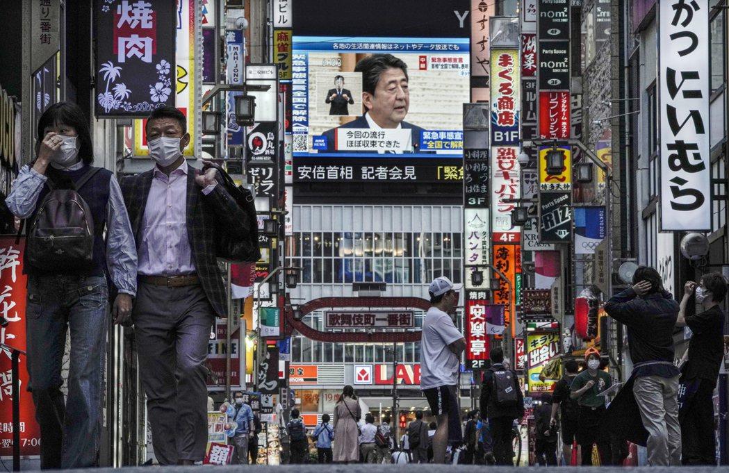 日本東京新宿歌舞伎町的大型電視幕,廿五日播放首相安倍晉三召開記者會宣布全國解除緊...