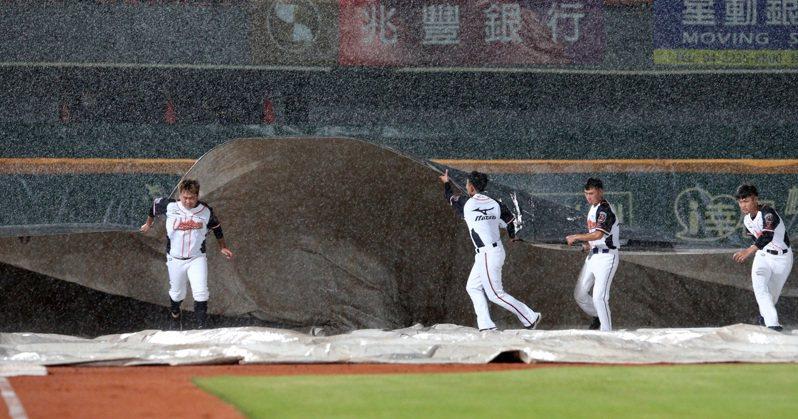 中華職棒昨天在台南進行獅對象例行賽,比賽到二局下半下起大豪雨,工作人員拉起帆布比賽也暫停。 記者劉學聖/攝影