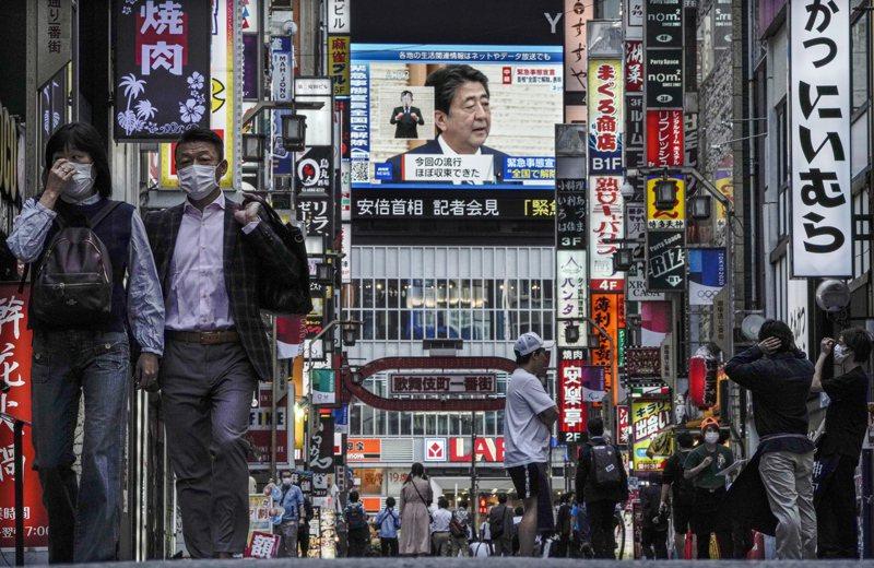 日本因應新冠肺炎疫情的「緊急事態宣言」解除,何時鬆綁入境管制備受關注,日本政府考慮的首波名單有台灣。圖為日本東京新宿歌舞伎町的大型電視幕,25日播放首相安倍晉三召開記者會宣布全國解除緊急狀態。歐新社