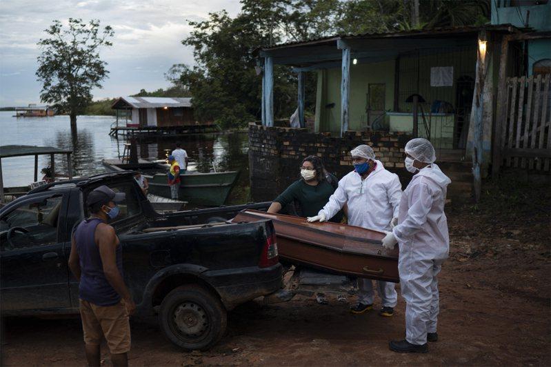 圖為巴西殯葬人員搬運疑因新冠肺炎死者棺木。美聯社