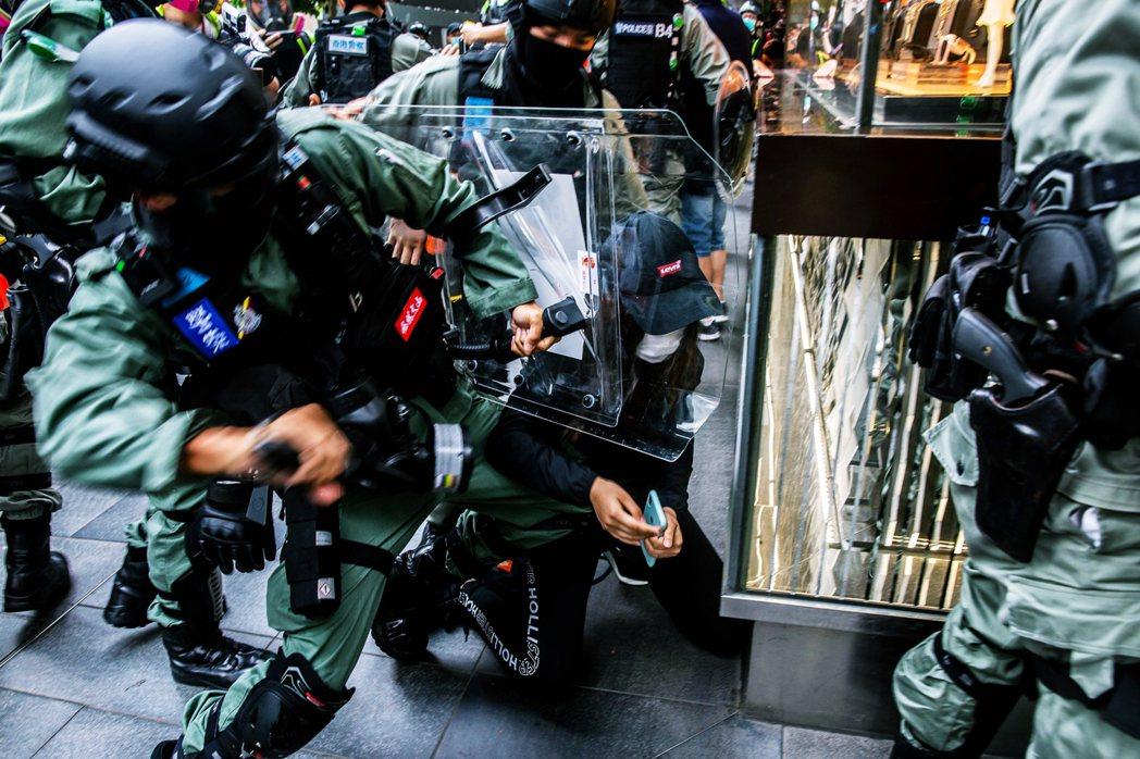 一名示威女性,被港警包夾圍捕,以警盾夾殺、衝撞倒地。 圖/法新社