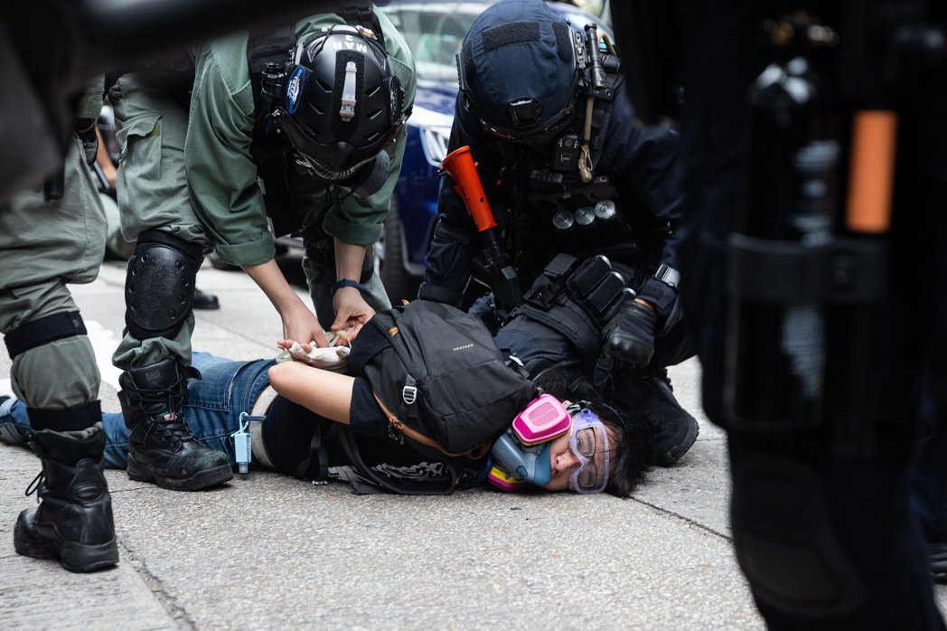 香港警察24日壓制一名上街抗議香港國安法的青年。  歐新社
