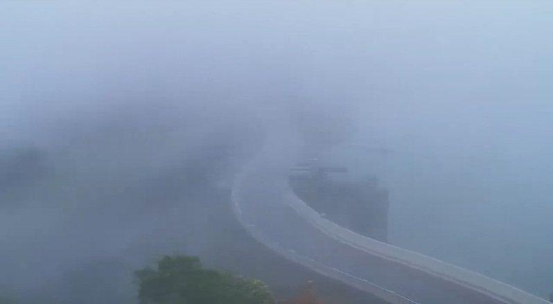 石門水庫壩頂上午10點繼續降雨,翡翠樓通往依山閣的路被雨勢和水氣籠罩。圖/桃園市觀光旅遊局即時影像