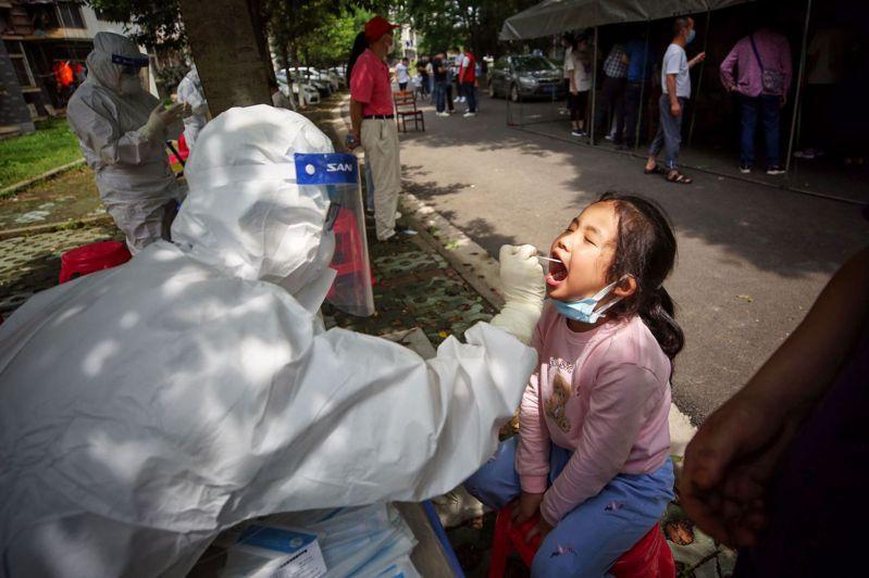 武漢市5月14日起展開新冠普篩,截至24日已900萬人受檢,醫療工作人員都在室外臨時採檢站工作。法新社