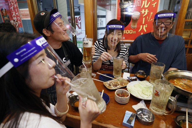 日本解除緊急事態宣言後居酒屋終於可延長營業,戴透明面罩喝酒成防疫新生活風景。(美聯社)