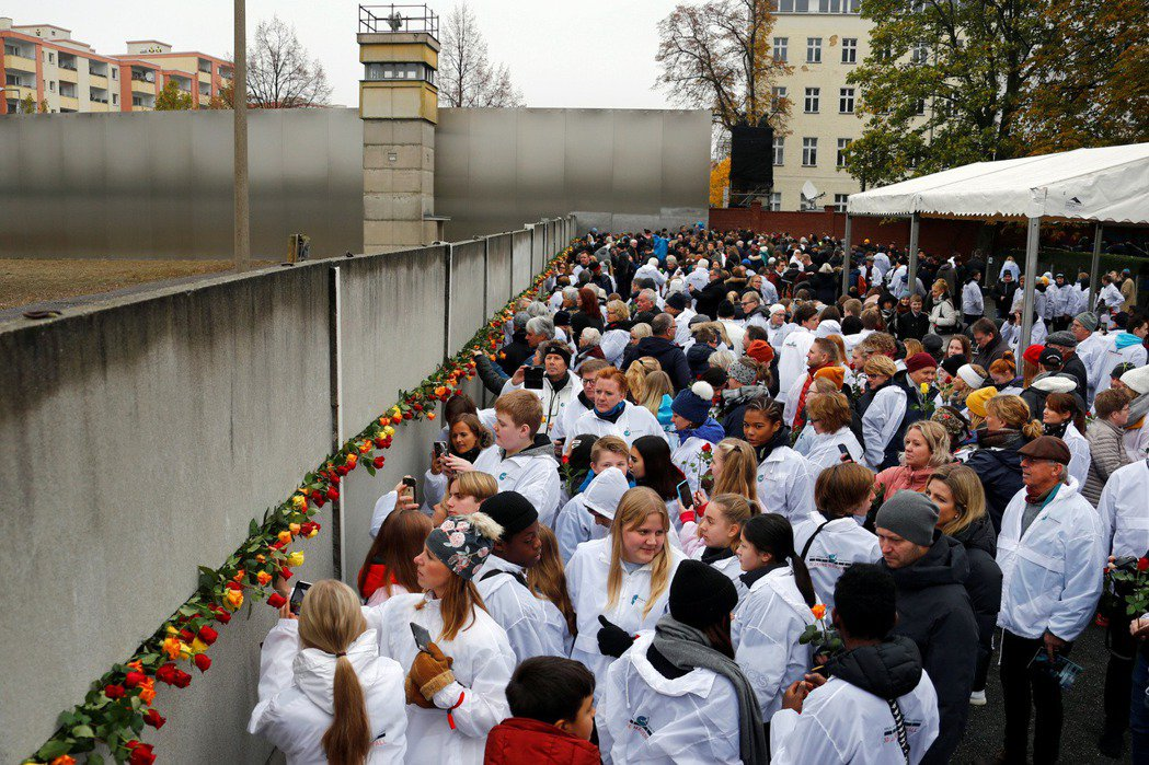 紀念柏林圍牆倒塌30周年,德國民眾獻上玫瑰花。攝於2019年11月9日。 圖/路透社