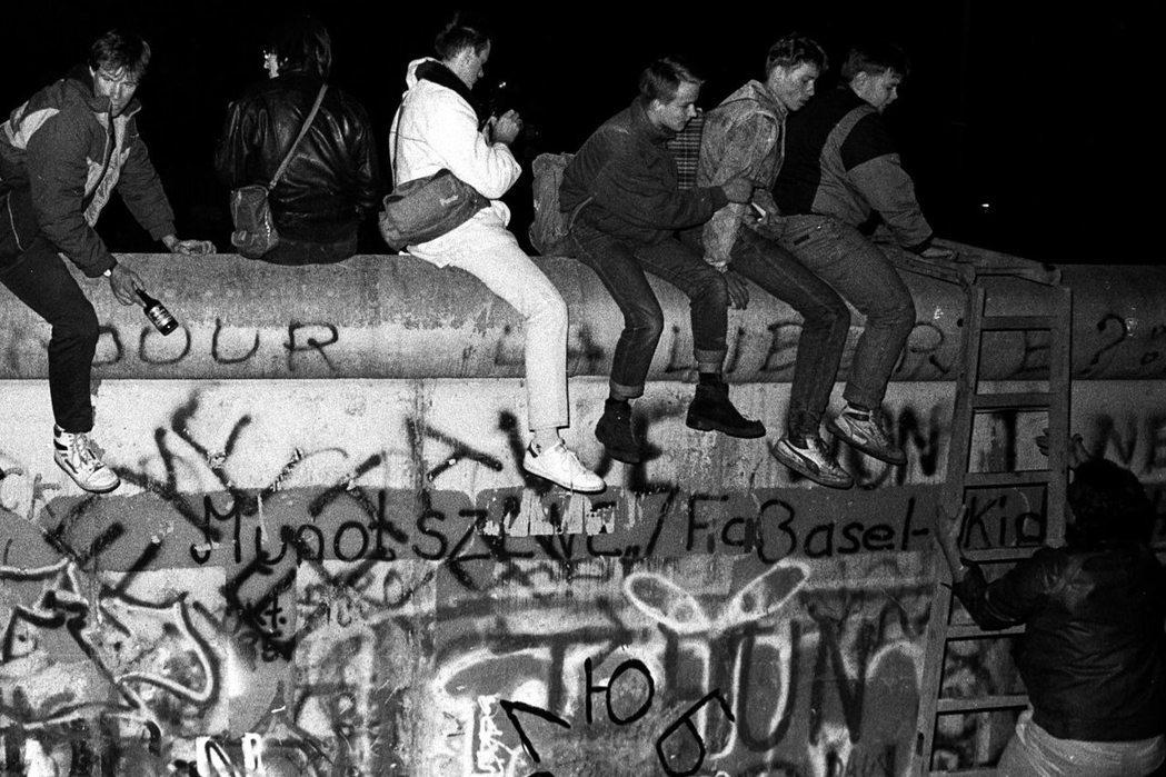區分、隔離與障礙的意象,也是柏林圍牆最為世人所記住的形象。圖為攀上圍牆塗鴉的西德居民。 圖/路透社