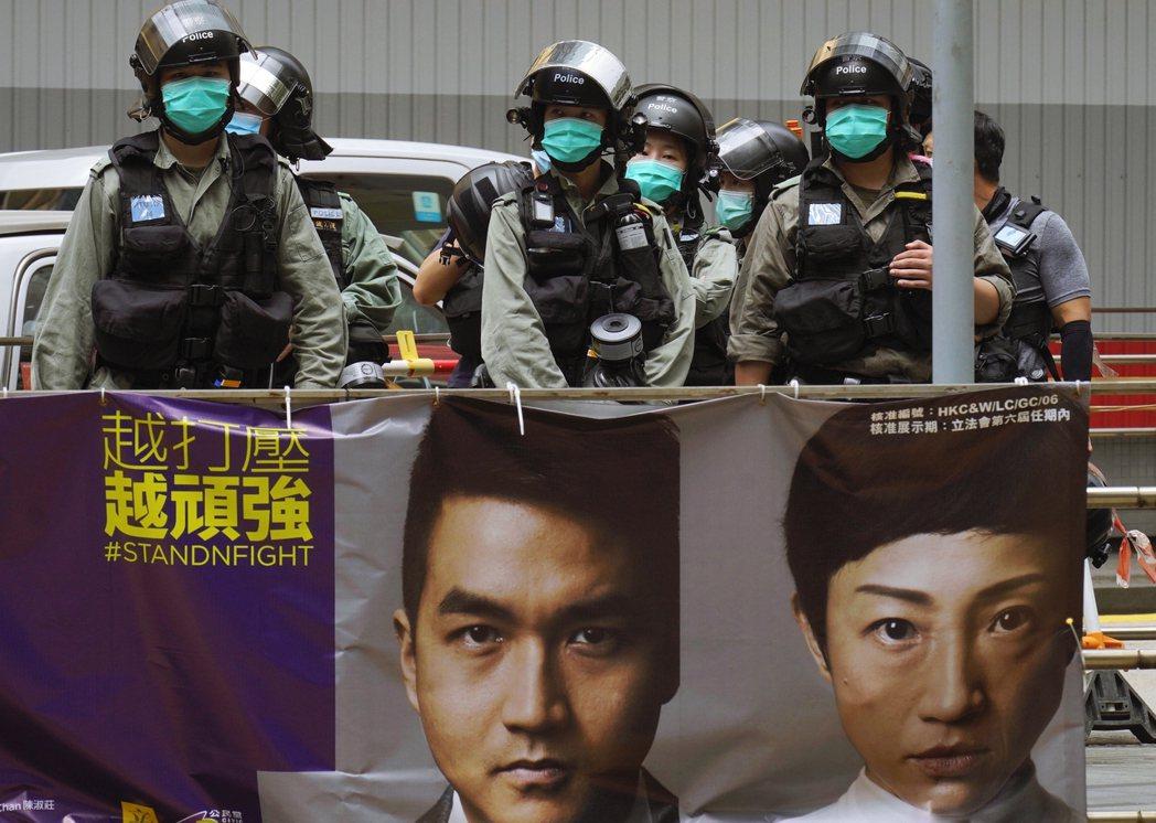 「越打壓越頑強。」港警與香港街頭的公民黨看板海報。 圖/美聯社