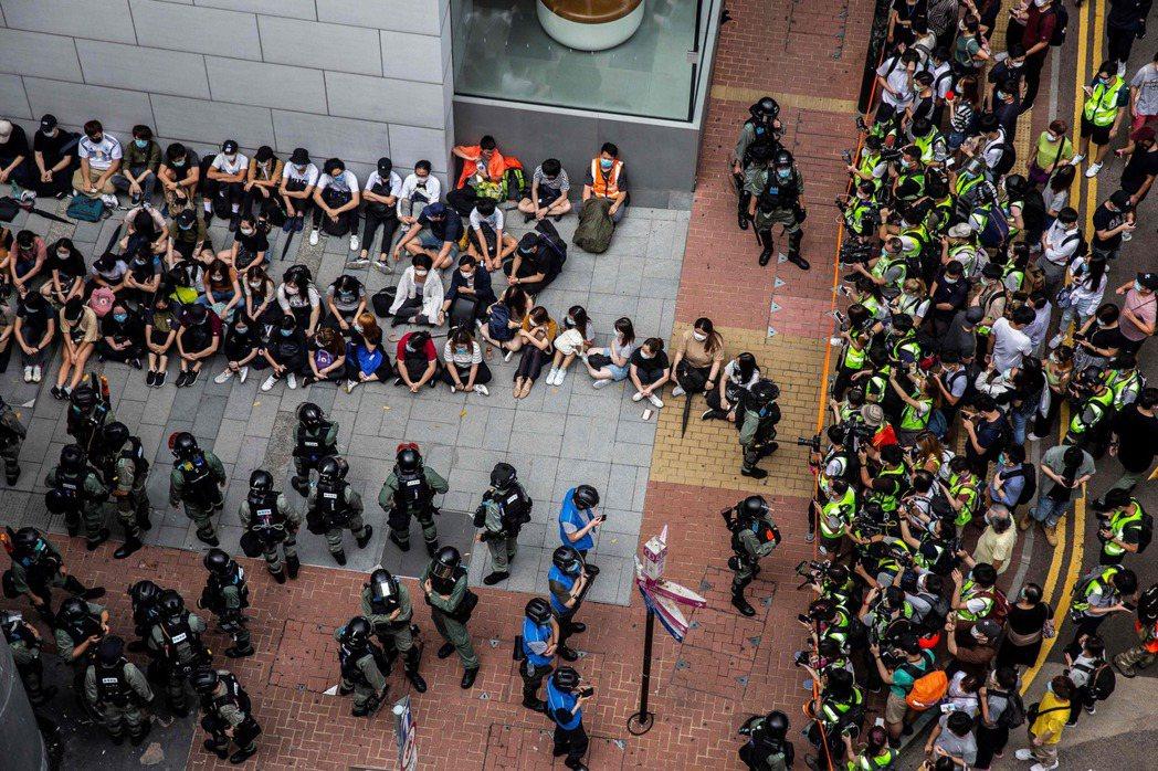 鎮暴警察拘捕集中一群示威者後,媒體(右)在旁拍攝觀看。(法新社)