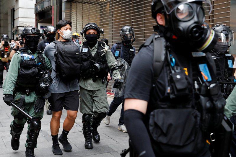 香港鎮暴警察廿七日在中環逮捕一名抗議國歌法二讀的示威者。(路透)