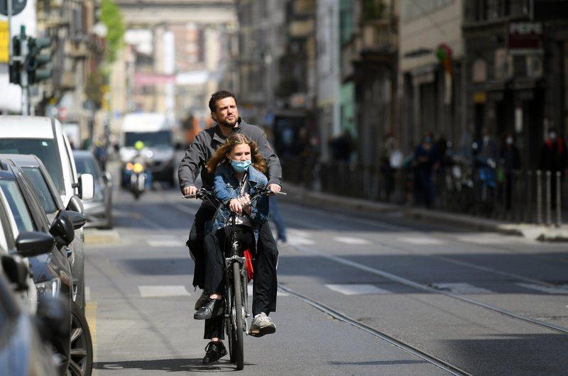 部分歐洲國家看見新冠疫情後的城市發展機會,義大利米蘭已提出「開放道路」計畫,將長達35公里的道路修建為自行車道與人行道。圖為一對米蘭父女4月18日共乘自行車外出。路透