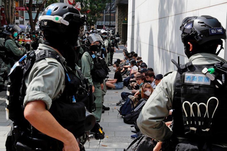 香港反政府示威人士27日被警察在街頭集中靠牆留置。  路透