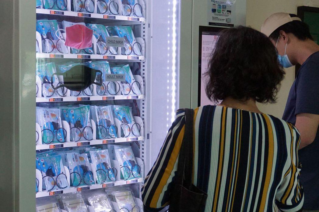 新加坡居民只要掃瞄身分證就能從自動販賣機免費取得可重複使用的口罩。法新社