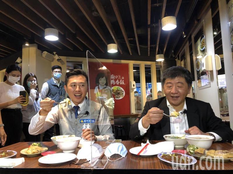 衛福部長陳時中(右)與新竹市長林智堅(佐)在有透明隔板的餐桌享用鴨香飯、荷包蛋、貢丸湯、炒鴨血、鴨腿肉等美食。記者王駿杰/攝影