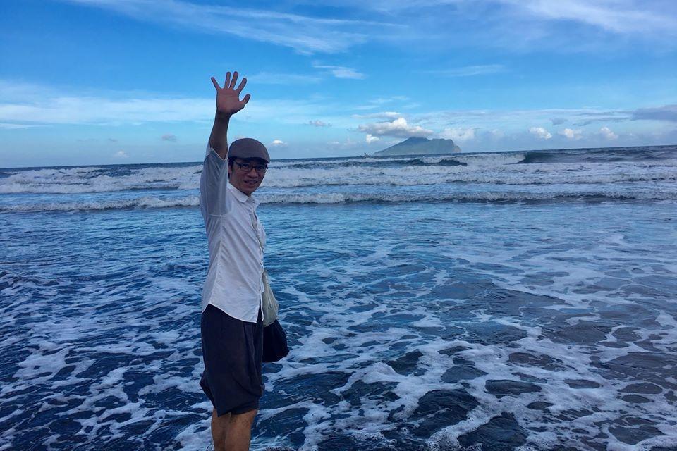 吳朋奉在海邊揮手像是道別。圖/摘自臉書