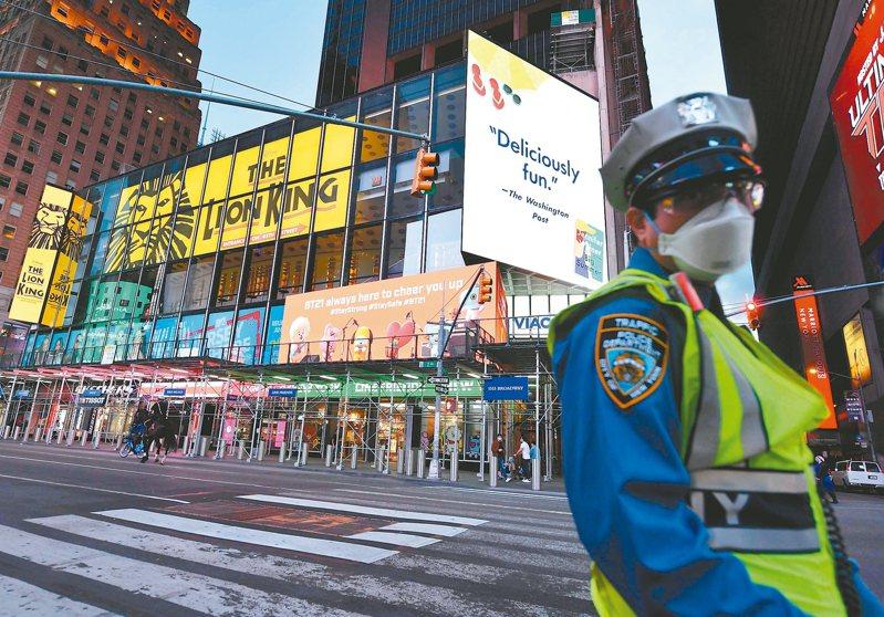 一名戴口罩的警察廿七日在紐約時報廣場巡邏。美國新冠肺炎疫情仍在延燒,死亡人數已經超過十萬人。 (法新社)