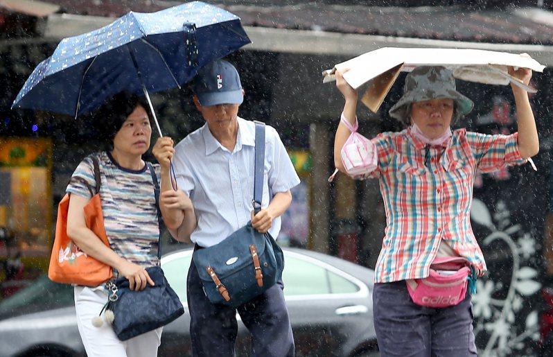 中央氣象局昨天對17個縣市發布大雨特報,台北市也受鋒面影響及對流雲系發展旺盛,午後下起雷陣雨,一名未帶雨具的路人過馬路時,索性將厚紙板撐在頭上遮擋。記者余承翰/攝影