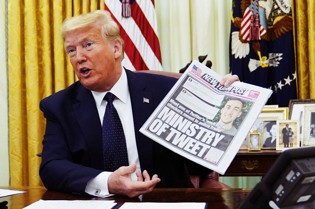 簽署行政命令之前,川普拿出了報紙,一邊為自己的「言論自由」與「被打壓」辯護。 圖...