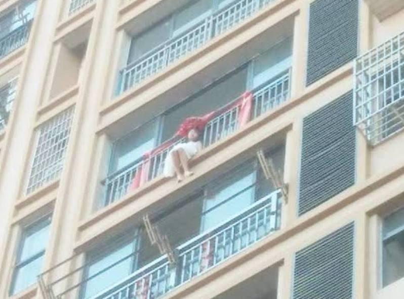 女童不滿媽媽偏心無預警爬出8樓窗邊,企圖跳樓輕生。圖擷自搜狐新聞