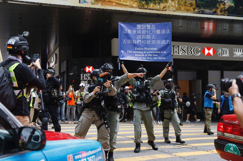 中共人大會議昨天通過「港版國安法」,蔡英文總統指示行政院提出「香港人道援助行動專案」,圖為香港民眾抗議,港警舉槍警告。美聯社
