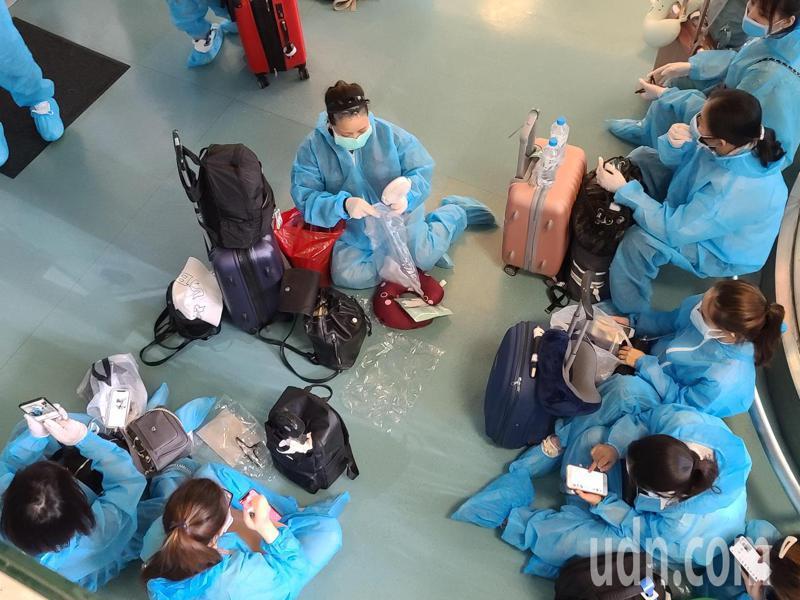 越南應民眾要求解除境管,由越南航空首次派遣專機來台接回僑民,所有旅客在上機前必須再次測量體溫才能登機,造成登機時間拉長,找不到座位的旅客坐在地上休息。記者鄭超文/攝影