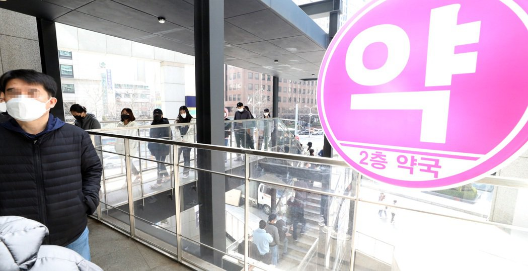南韓將從6月起停止以身分證尾號買口罩制度,圖為首爾民眾在一家藥局前排隊買口罩情形...