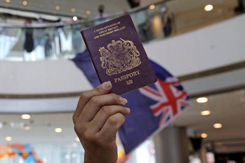 香港民眾29日在商場拿著英國國民海外護照和香港殖民時代旗幟,抗議大陸人大決定制定港版國安法。圖/美聯社