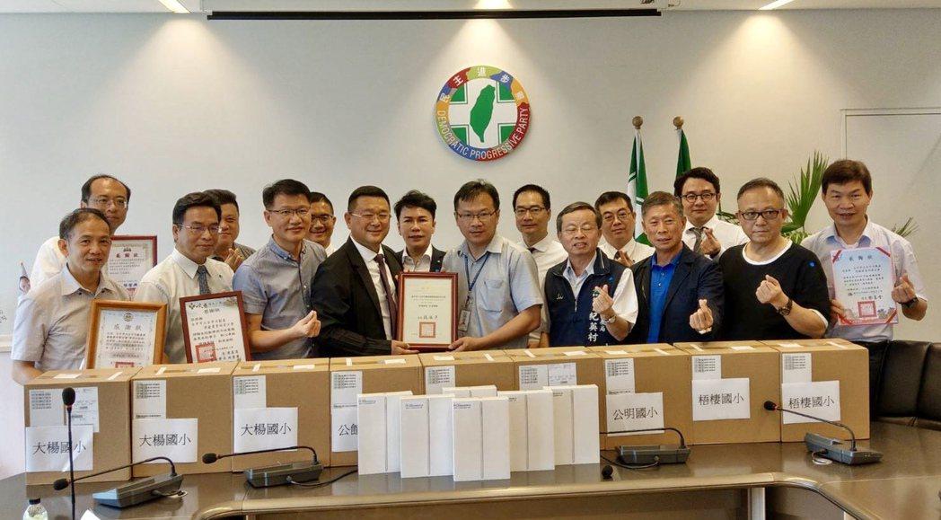 大台中不動產開發公會理事長王至亮(前排左四)代表捐出100台IPAD與配件,幫助...