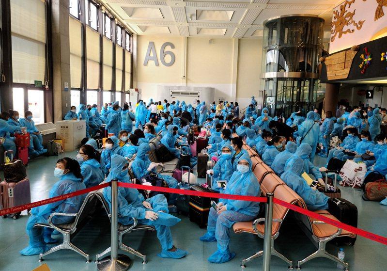 越南昨天派遣專機來台接回三百多名僑民,桃機第一航廈候機室擠滿人潮,旅客須穿著藍色防護裝備才能登機。 記者鄭超文/攝影