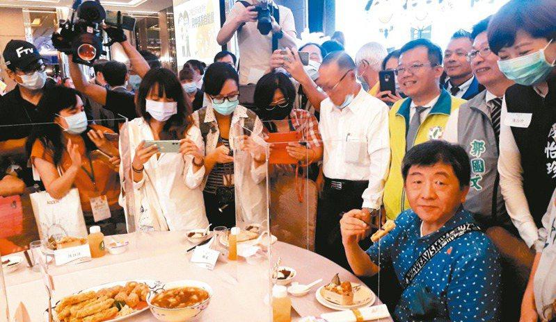 衛福部長陳時中(穿藍衣坐者)昨天再度展開樂活防疫之旅,晚間在台南吃飯時,不斷有民眾包圍拍照或自拍。 記者周宗禎/攝影