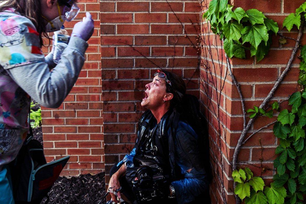 一名新聞記者,在警方發射催淚彈與橡膠子彈的混亂場面中,引發不適。有抗爭群眾的醫護...