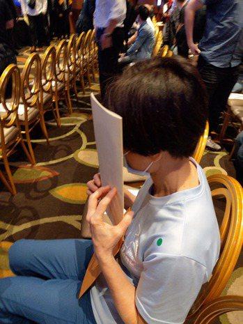友訊董事長胡雪被解任後,以議事手冊遮臉,不發一言,離開會場。 記者黃晶琳/攝影