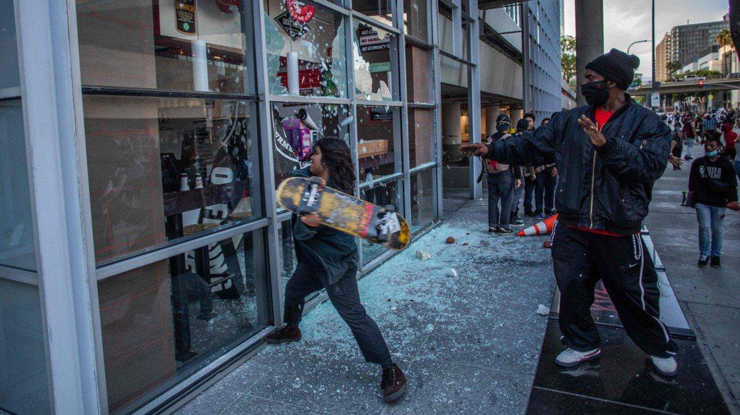 全美各地抗議警察濫權施暴,洛杉磯城中區有示威者用滑板猛砸餐廳玻璃洩憤。 法新社