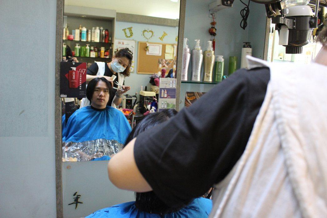 20歲男學生蘇己耀今天剪下30公分長的長髮捐出。記者林敬家/攝影