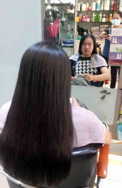 20歲男學生蘇己耀花2年時間留長髮打算捐髮,今天請美髮師為他剪髮。記者林敬家/攝...
