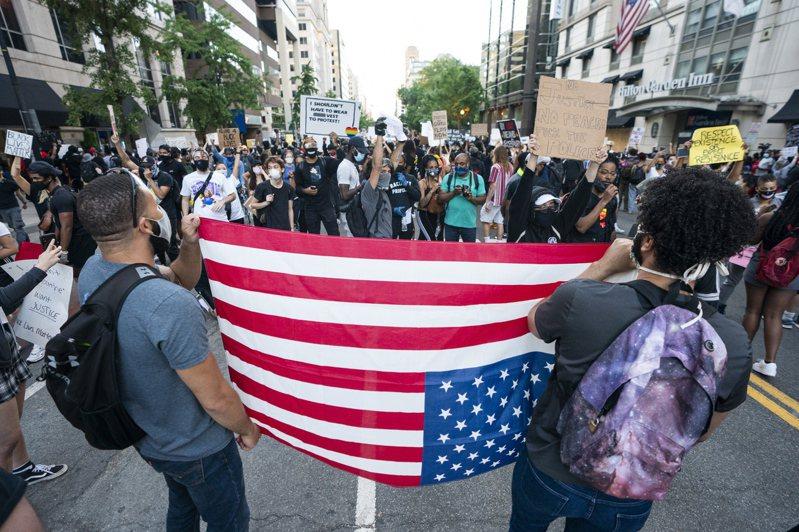 5月31日白宮附近有示威者拿著顛倒的美國國旗參加抗議活動。歐新社