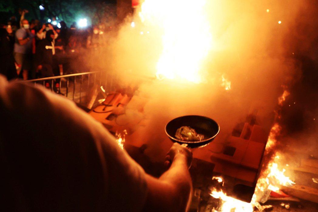 全美反警暴示威延燒,有示威者借用暴動點燃的街頭之火,順手煎起了培根。 圖/路透社