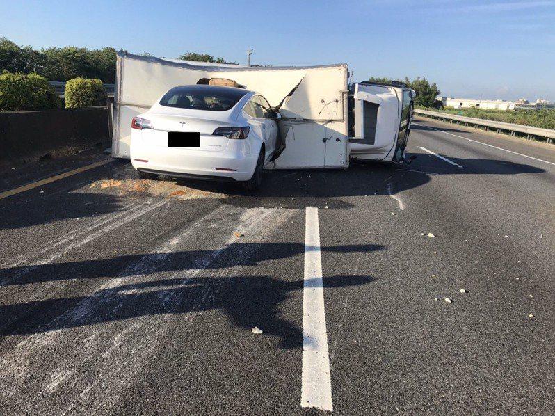 一輛食品貨車昨天上午倒在國道一號南向二六八點三公里處內側車道上,後方一輛特斯拉轎車撞進貨車車廂。 圖/警方提供