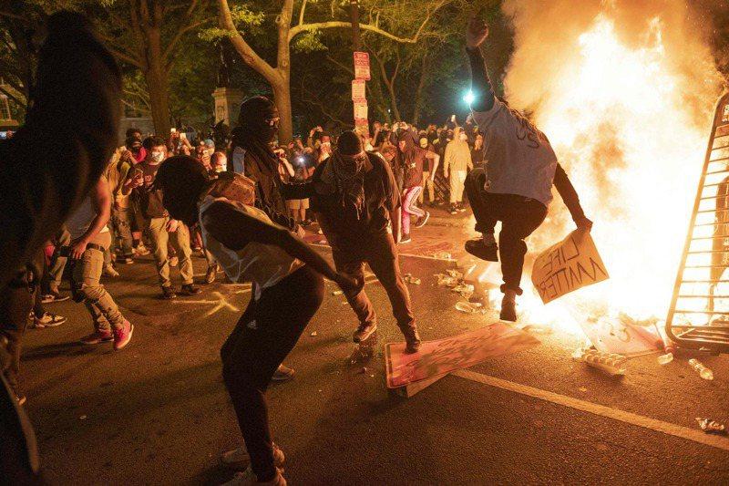 一名非裔5月25日遭美國白人警察壓頸喪生後,全美各地持續出現暴力示威。圖為5月31日在白宮附近的抗議中,示威者踩踏道路標誌。 法新社