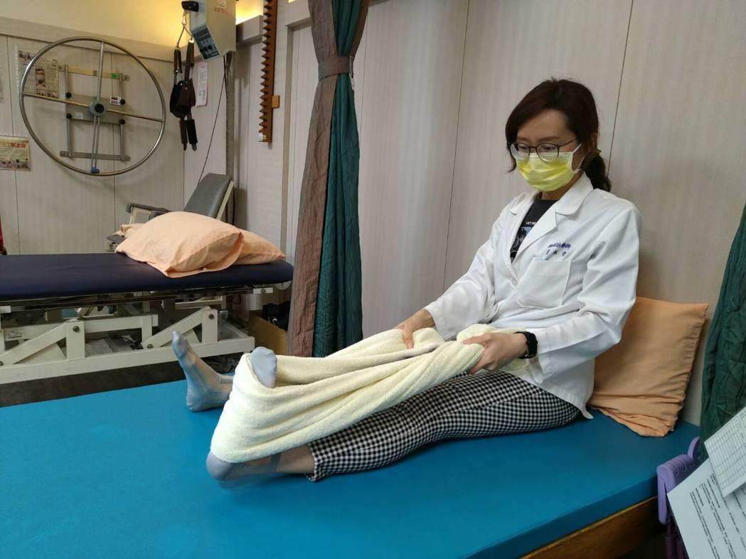 將毛巾固定於腳板,膝蓋伸直,雙手向後拉緊毛巾使腳板往上翹。圖/物理治療師黃佩安提...
